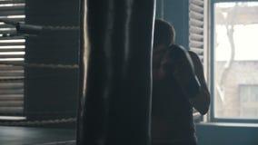 Homme caucasien dans des gants de boxe frappant le sac de sable durement banque de vidéos