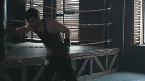 Homme caucasien dans le sac de sable à gants de boxe dur dans le mouvement lent clips vidéos