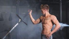 Homme caucasien de forme physique soulevant la tôle forte du barbell pendant la séance d'entraînement dans le gymnase banque de vidéos