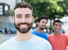 Homme caucasien heureux avec la barbe avec deux amis dans la ville Photo libre de droits
