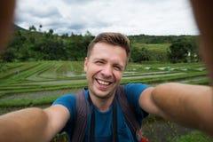 Homme caucasien heureux avec le voyage de sac à dos dans la plantation de riz et le selphie de fabrication photos stock