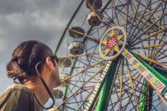 Homme caucasien observant la roue de ferris photo stock