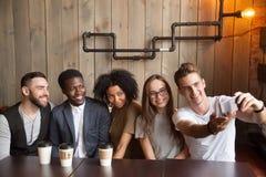 Homme caucasien prenant la photo de groupe avec les amis divers en café Photos libres de droits