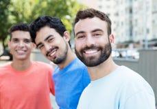 Homme caucasien riant avec la barbe avec deux amis dans la ville Images stock