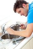 Homme caucasien réparant un bassin de cuisine Images stock