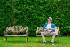 Homme caucasien s'asseyant sur le livre de chaise et de lecture Photo libre de droits