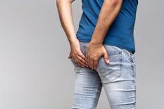 Homme caucasien tenant ses fesses dans des jeans de denim Photographie stock libre de droits