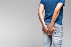 Homme caucasien tenant ses fesses dans des jeans de denim Images stock