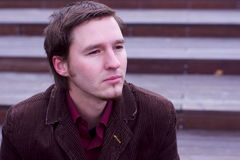 Homme caucasien triste ou rêvant l'expression par des escaliers Photos stock
