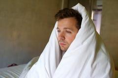 Homme caucasien triste s'asseyant sur son lit avec sa tête couverte de couverture Images stock