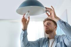 Homme changeant l'ampoule dans la lampe pendante photographie stock libre de droits