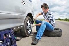 Homme changeant la roue de secours de la voiture Photographie stock