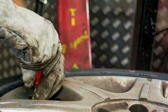 Homme changeant la valve de pneu Image stock