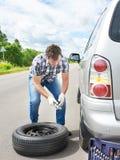 Homme changeant une roue de secours de voiture Photographie stock