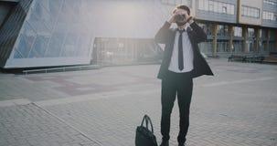 Homme charismatique d'affaires dans un costume prenant un café derrière le centre d'affaires banque de vidéos