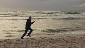 Homme chassant des autres sur la plage banque de vidéos