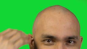 Homme chauve avec la tête émouvante de demi visage sur le fond vert banque de vidéos