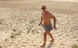 Homme chauve avec un coffre nu nu, dans les troncs de natation rayés ou le s Image stock