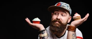 Homme chauve barbu heureux tenant deux g?teaux cr?mes sur le fond noir photographie stock