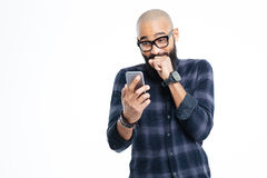 Homme chauve d'afro-américain gai employant le smartphone et rire Photographie stock