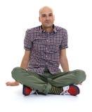 Homme chauve occasionnel s'asseyant avec des jambes croisées image libre de droits