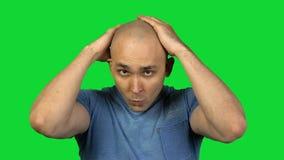 Homme chauve principal émouvant sur le fond vert clips vidéos