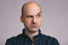 Homme chauve sérieux avec le sourcil augmenté photographie stock libre de droits