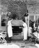 Homme chez la femme à leur barbecue dans l'arrière cour (toutes les personnes représentées ne sont pas plus long vivantes et aucu Photos stock