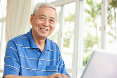 Homme chinois aîné à l'aide d'un ordinateur portatif à la maison Image libre de droits