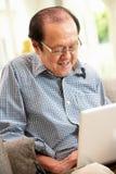 Homme chinois aîné à l'aide de l'ordinateur portatif tout en détendant Photo stock