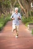 Homme chinois aîné courant en stationnement Images stock