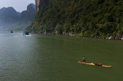 Homme chinois dans un radeau et bateaux avec des touristes croisant dans Li River près de la ville de Yangshuo en Chine Photo stock