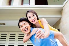 Homme chinois portant son ferroutage de fille à la nouvelle maison image stock