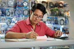 Homme chinois travaillant dans la boutique informatique vérifiant des factures et des impôts Photographie stock libre de droits