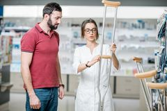 Homme choisissant des béquilles dans la pharmacie Photo libre de droits