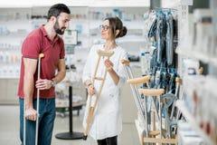 Homme choisissant des béquilles dans la pharmacie Photographie stock