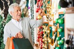 Homme choisissant des boules de Noël Images libres de droits