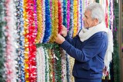Homme choisissant des tresses dans le magasin de Noël Image stock