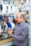 Homme choisissant le câble dans le magasin de ménage Images libres de droits