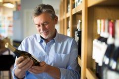 Homme choisissant le vin photographie stock