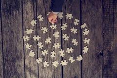 Homme choisissant un morceau de puzzle Photographie stock libre de droits