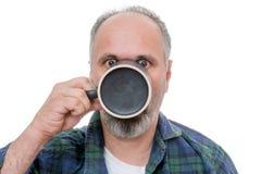 Homme choqué avec la tasse devant le visage Photographie stock