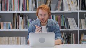 Homme choqué et stunned avec les poils rouges travaillant sur l'ordinateur portable photographie stock libre de droits