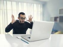 Homme choqué lisant le message sur l'ordinateur dans le bureau photos stock