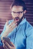Homme choqué regardant le smartphone Photographie stock