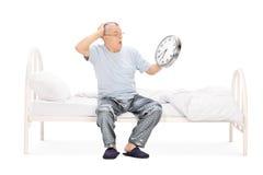 Homme choqué s'asseyant sur le lit et tenant une horloge Images stock