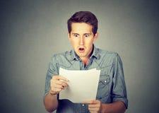 Homme choqué tenant quelques documents images libres de droits