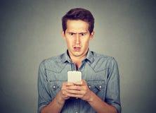 Homme choqué vérifiant le téléphone portable photographie stock