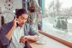 Homme choqué vérifiant le temps, parlant à son téléphone photographie stock libre de droits