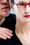 Homme chuchotant méchamment le venin chez l'oreille de la femme Images libres de droits